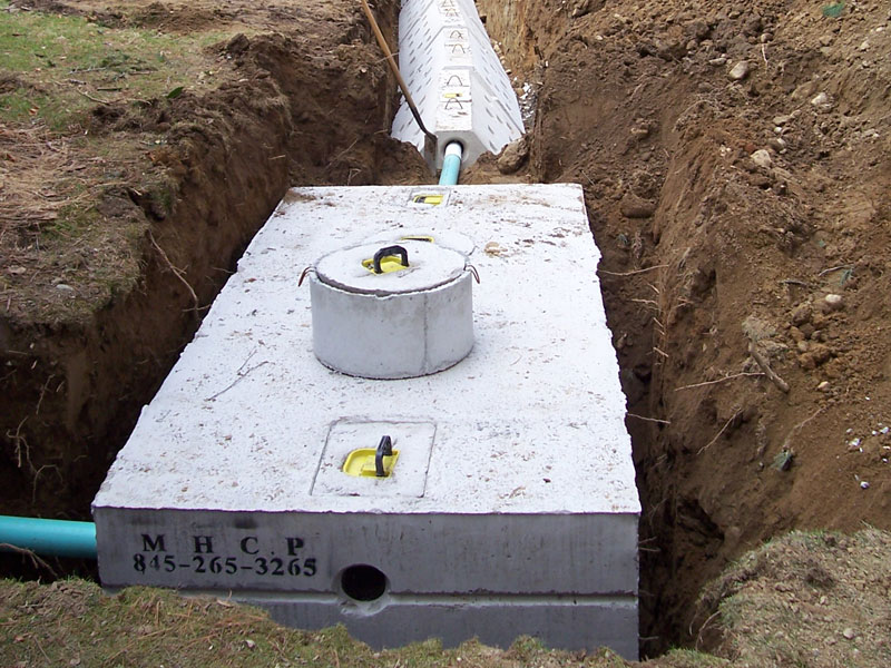 Septic tank in ground with pipes going into it from a trench